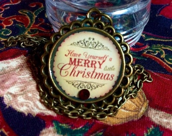 A Merry Little Christmas Pendant in antique bronze with cherry red crystal accent