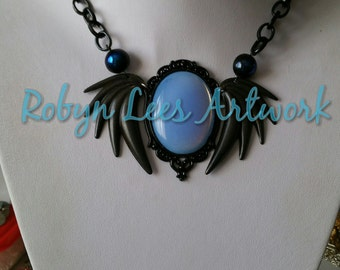 Large Blue Stone Cabochon Necklace with Gothic Black Swan Wings, Metallic Blue Czech Glass Beads and Victorian Style Frame on Black Chain