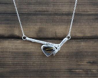 Silver cork oak twig pendant with tiger eye.