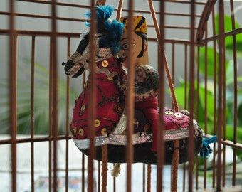 Maharajah on horseback in a wooden cage