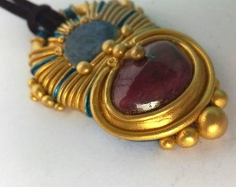 Polymer clay pendant with ruby and blue stone