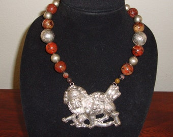 Chinese Fu Lioness pendant strung with varicolored brown-red beads and silver beads