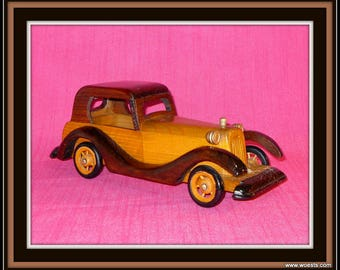 Decorative model of a antique car made of woodcarvings. Vintage Handcarved wooden oldtimer carved  of wood. Handmade car replica. Gift idea
