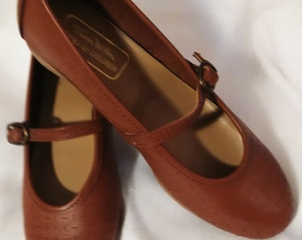 Deep caramel Mary Jane flat with  small metal buckle over instep. Pricked leather uppers for added interest. Rubbery non slip sole.Sz 2 1/2