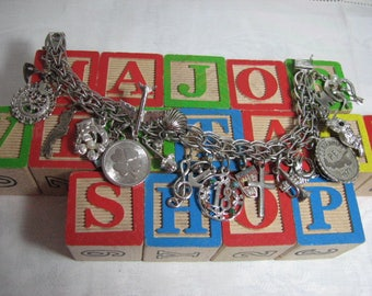 Circa 1950 Sterling silver charm bracelet with twenty-one charms , eight inches  long.