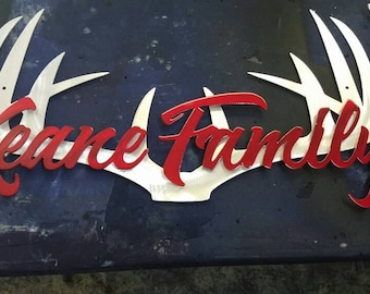 """Family name or hunting camp name over antlers. Can have name made over any image. All aluminum. 22"""""""