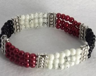 Stretch bracelet of glass beads with metal dividers. Red, black and white