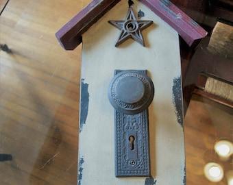decorative door knob and cast iron star on a mini house wall art