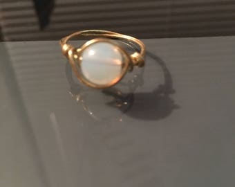 Gold wire wrapped ring with an iridescent glass bead.