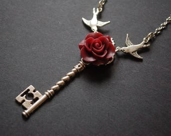 Burgundy flower swallows key necklace