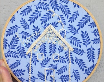 """Handmade embroidery hoop with """"Home""""."""