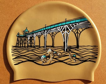 Swim cap, Clevedon swimming hat in gold, lilac or orange - featuring a drawing of the Clevedon Pier and swimmers. Swimmer gift