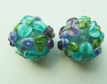 Glass lampwork bead set in transparant turquoise with raised flower decoration