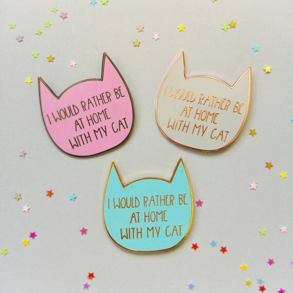 Three pin badges, in pink, blue or white, all saying 'I would rather be at home with my cat'