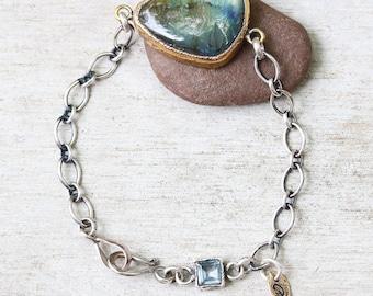 Teardrop cabochon labradorite bracelet in brass bezel setting with blue topaz secondary gemstone and oxidized sterling silver chain
