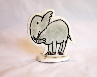 small porcelain elephant with underglaze drawing, overglaze decals and bright gold luster