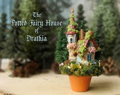 Glenny Lipton's Fairy Cottage - Potted Fairy House - Miniature Woodland Stone House -Tile Roof, Pine Trees, Wildflowers, Bench, Window Boxes