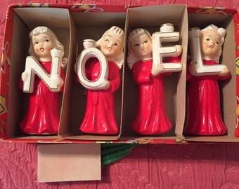 Christmas candle holde angels spells NOEL