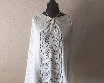 White poncho knitting hand