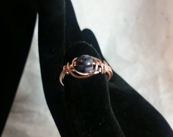 Wire wrapped ring with purple bead and rose wire.