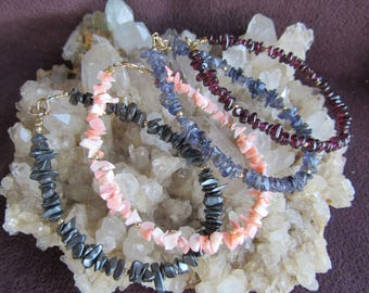 Bracelets   done in 4  gemstone chip bracelets , hematite, coral, iolite, garnet, all 7 inch, all 12k gold filled beads and clasp.