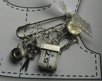 Sewing themed brooch.
