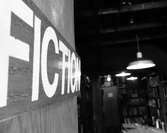 FICTION: Book stack sign in a used bookstore in Boston, MA. Black and white New England photography; library; office; study; bedroom