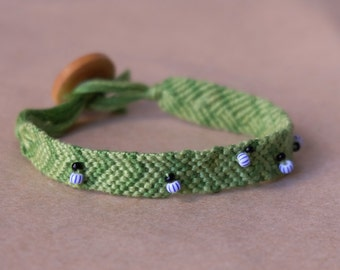 Friendship bracelet with bugs, leaf green woven bracelet with chunky button