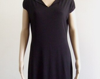 The p'tite short black sheath dress with short sleeves and her cleavage cleft