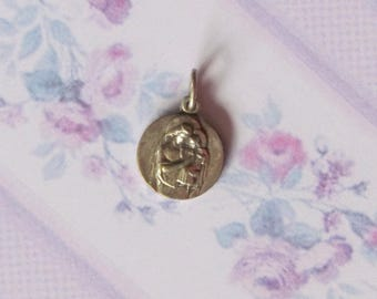 Antique pendant of Mother Mary holding Baby Jesus