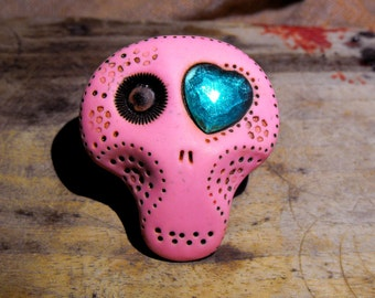 Sugar skull brooch in hot pink with a blue heart his eye.