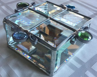 A clear beveled glass box with a quilted looking lid with blue and green glass nuggets