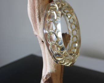 Vintage 1980s chunky clear lucite bangle bracelet, inset with gold tone chain. Imported from the UK