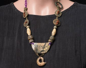 The Forever Machine, antique shoelace studded with rustic ceramics and pearlized ammonite, hanging from purple silk wrapped chain