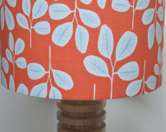 Handmade lampshade using repeated frond leaf patterned fabric in white and grey on tangerine