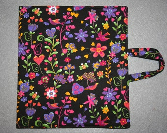 Art and activity bag, travel tote, pencil case with zip, drawing and note pad holders, A5. Black with multi coloured flowers.