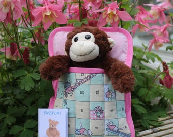 Monkey in a sleeping bag ready to travel. Overnight teddy complete with passport.