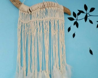 Macrame wall hanging on driftwood with feathers
