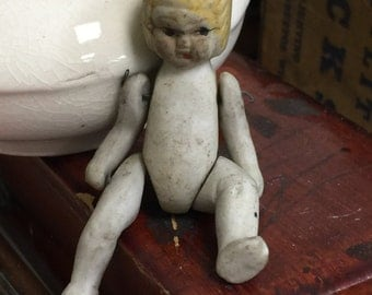 Antique all bisque doll with fixed hair and neck has movable arms and legs