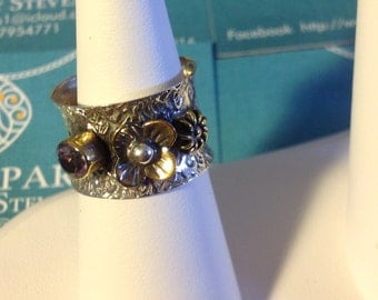 Beautifully hand crafted silver ring with one set amethyst and two brass flowers ,it's decorated all the way back