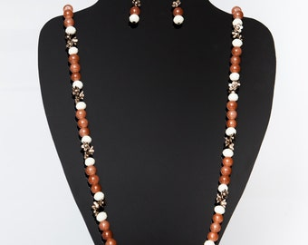 Brown and cream beaded necklace, decorated with small bronze flowers.
