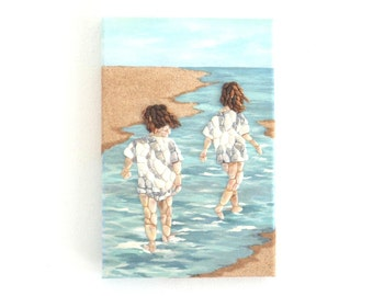 Two Young Girls Paddling in Seashell Mosaic with Sand