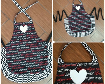 "3 or 4 year old mini child apron. ""Love is all you need"" wording on black print. Black and white chevron frills. Heat press white heart."