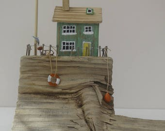Solitary green driftwood cottage. Uniqe clifftop cottage made from upcycled North East beach driftwood.