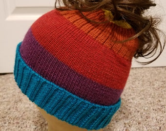 Messy bun hat knit in rainbow colors with super soft washable wool.