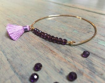 Golden bangle, purple pearls and pompon