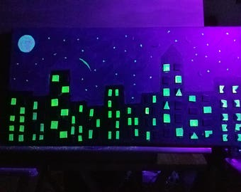 This painting was done with glow-in the dark paint so when you hold it up to a black light, the stars, the moon and the windows light up!