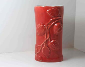 Handmade orange vase, decorated with fizalis flowers motifs. Colourful adornment for interior.