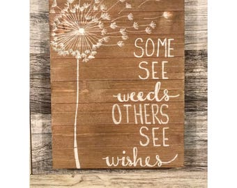 Some see weeds, others see wishes wooden sign
