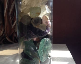 A jar of different types of raw gem stones